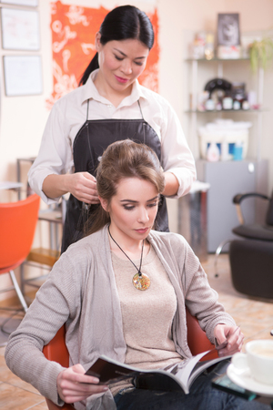 hairdressing saloon: Pretty lady reading magazine while having her hair cut or done by beautiful barber girl in hairdressing saloon. Stock Photo