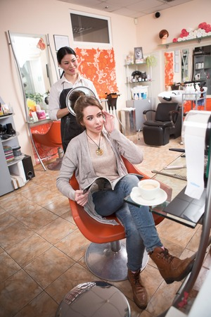 hairdressing saloon: Beautiful lady reading magazine while having her hair dobe by hairdresser in hairdressing saloon. Closeup picture of cup of coffee. Stock Photo