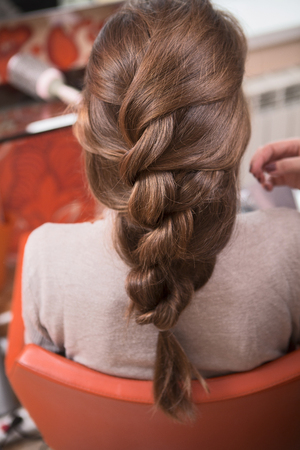 hairdressing saloon: Beautiful lady having weave braids while sitting in hairdressing saloon. Stock Photo