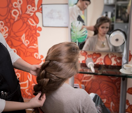 hairdressing saloon: Braided braids blonde at beauty salon. Closeup picture of beautiful lady sitting in chair and looking at mirror while hairdresser making braid in hairdressing saloon.