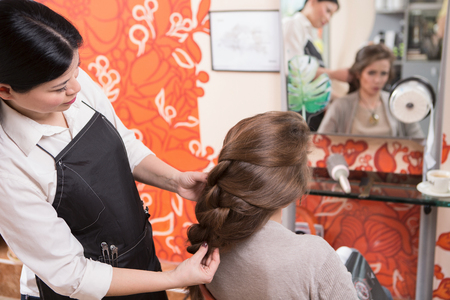 coiffeur: Closeup hairdresser coiffeur makes hairstyle. Hairdresser makes braid in beauty salon. Stock Photo