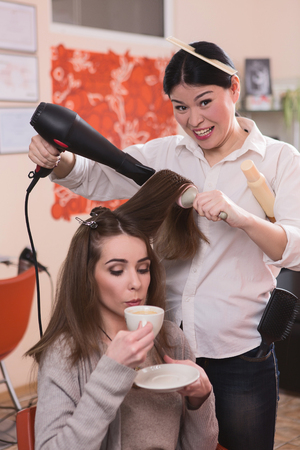 hairdressing saloon: Picture of beautiful lady sitting in chair, drinking coffee and having her hair washed in hairdressing saloon. Fashion and beauty concepts.