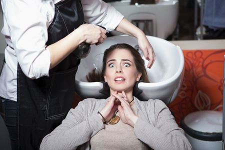 hairdressing saloon: Portrair of frightened beautiful lady while having her hair wash in hairdressing saloon. Pretty lady looking at camera.