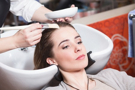 stylish girl: Barber girl combing her hair in beauty saloon. Beautiful lady having her hair washed by hairdresser in hairdressing saloon.
