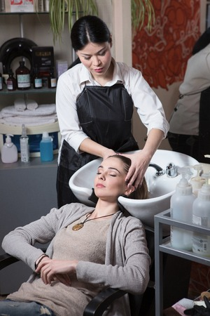 hairdressing saloon: Side view of beautiful hairdresser washing hair to her client lady in hairdressing saloon. Client sitting with her eyes closed.