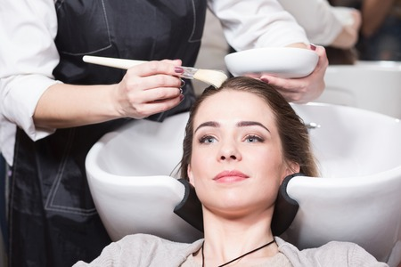 saloon: Beautiful lady having her hair washed by hairdresser in hairdressing saloon. Barber girl combing her hair in beauty saloon.