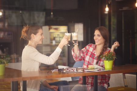 best friends girls: Toned picture of best friends girls having round or cheers while sitting in cafe or restaurant. Women drinking delicious coffe.