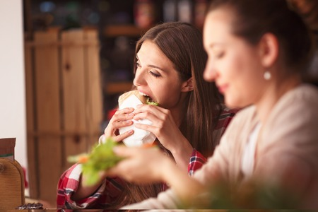 best friends girls: Toned picture of best friends girls spending free time in cafe or restaurant. Beautiful ladies eating vegetarian dishes and foods. Stock Photo
