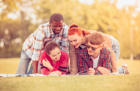 Picture of happy friends having free time on picnic. Cheerful people lying on picnic rug and smiling.