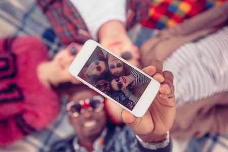 Foto de los mejores amigos que hacen autofotos en el teléfono móvil o inteligente al pasar el tiempo libre en picnic en Parklane. Foto de archivo