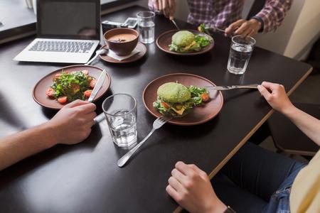 personas comunicandose: Foto de detalle de platos vegetarianas representados en la mesa de madera negro en el restaurante vegetariano o un caf� mientras que las personas de negocios que comunica. Foto de archivo
