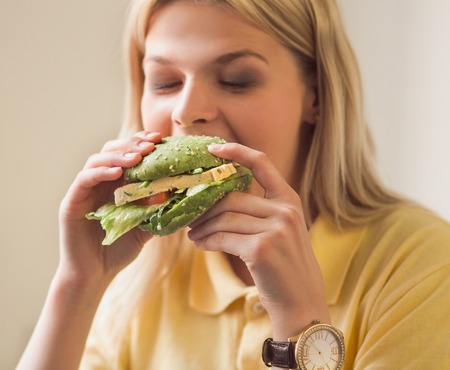 Closeup image of blond woman eating vegan burger in vegan restaurant or cafe.
