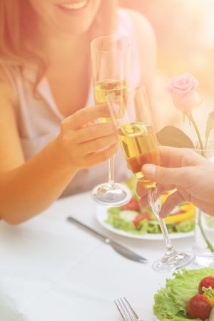 Toned picture of couple drinking wine from glasses while spending time in cafe or restaurant by sea.