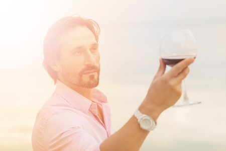 Toned picture of sommelier analyzing glass of red wine isolated on blue sky background. Stock Photo