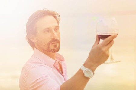Toned picture of sommelier analyzing a glass of red wine isolated on blue sky background.