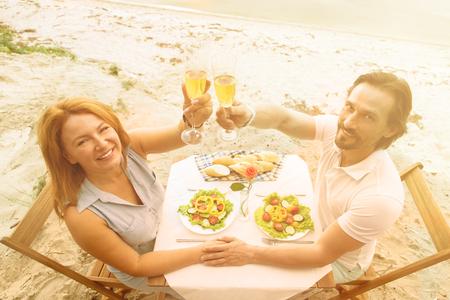 Imagem tonificada de homem bonito e mulher bonita olhando a câmera. Feliz casal sênior passando tempo no restaurante ou café pelo mar.