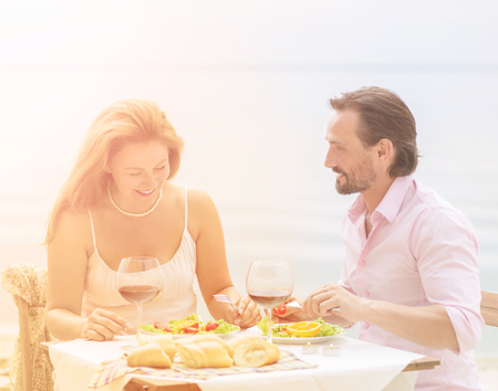 romantic beach: Toned picture of beautiful couple resting in restaurant or cafe by sea. Handsome man and beautiful woman having lunch or dinner with delicious red wine.