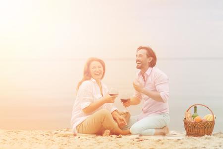 Getönten Bild paar lachend am Strand mit Picknick. Schöner Mann und schöne Frau in der Liebe halten Gläser mit köstlichen Rotwein isoliert auf Meer. Standard-Bild