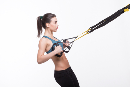 Beautiful lady training with suspension trainer sling or suspension straps isolated on white background in studio.