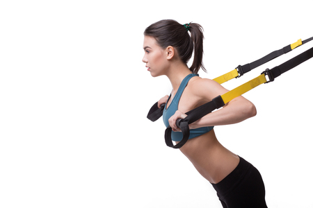 Beautiful woman exercising with suspension straps alone in studio. 스톡 콘텐츠