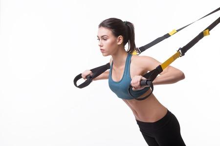 schöne Frau mit Aufhängebänder allein im Studio trainieren. isoliert auf weißem Hintergrund