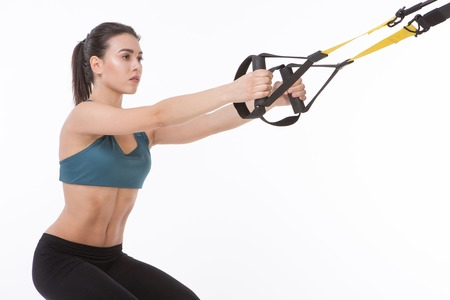 Closeup picture of beautiful lady training with suspension trainer sling or TRX in studio.