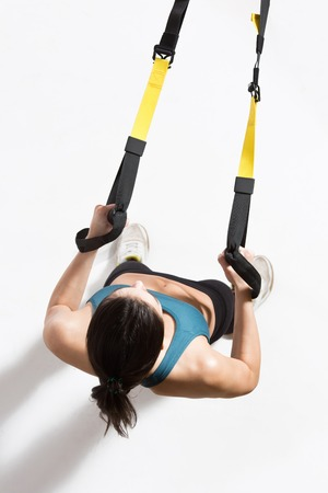 Top view of fitness trainer lady exercising on suspension trainer sling or suspension straps in studio.