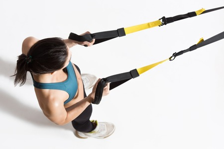 Top view of pretty young lady training upper body on suspension trainer sling.