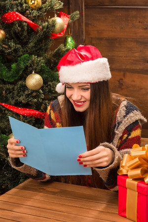 santa clause hat: Happy and beautiful girl in Santa Clause hat reading New Year and Christmas congratulation.