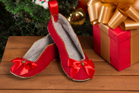 Close-up of red house slippers lying near New Year and Christmas presents and gifts. Stock Photo