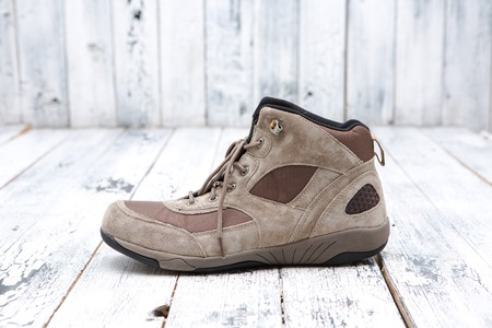 shoestring: Footwear concept. A brown mens boot represented on wooden background. A boot with shoe-string sands.