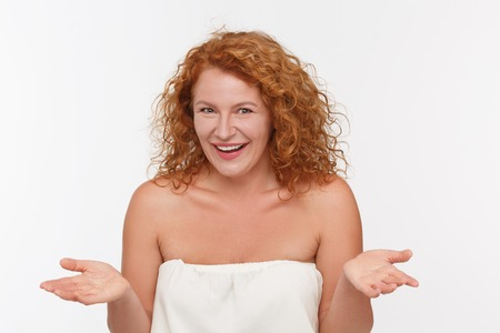 Portrait of cunning mature of middle aged woman in white dress posing isolated on white.