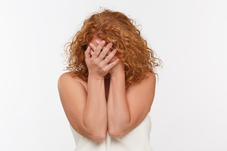 shoked: Beautiful red haired lady closing her face with hands isolated on white background. Stock Photo