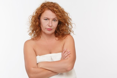 distrustful: Portrait of distrustful mature woman posing with her arms crossed or folded isolated on white background in studio.