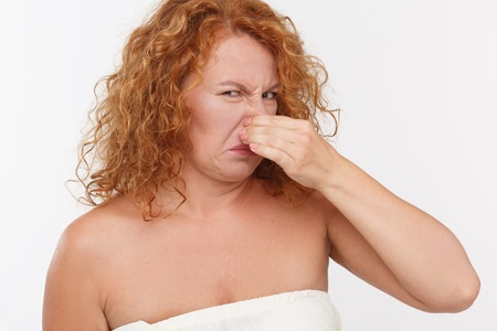 Picture of mature woman holding her nose isolated on white background in studio.