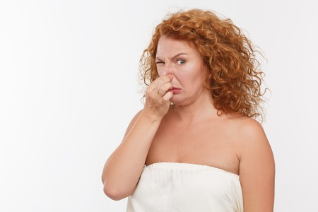 intolerable: Mature woman holding her nose because of bad smell isolated on white background.