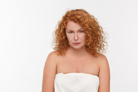 a situation alone: Picture of begging mature or senior woman with red hair looking at camera while posing isolated on white background in studio.