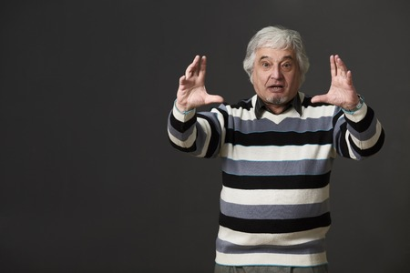 brainy: Professor man of university or college giving two hands while explaining new material to students or pupils isolated on black background in studio. Stock Photo