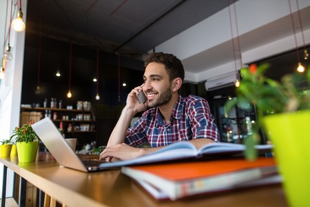 revision: Picture of handsome student sitting in front of laptop computer and speaking over mobile or smart phone. Stock Photo