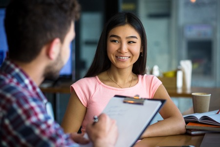 Picture of beautiful Korean or Asian lady having interview in restaurant. Handsome man asking her questions and writing something on clipboard.