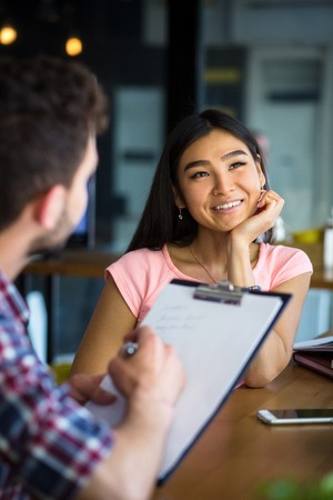restaurant questions: Beautiful lady having interview in restaurant or cafe. Man writing her CV and asking many questions.