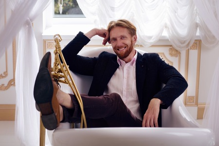 romantic man: Picture of happy smiling rich blond man in expensive apartments. Cheerful young man lying in bath and looking at camera. Stock Photo