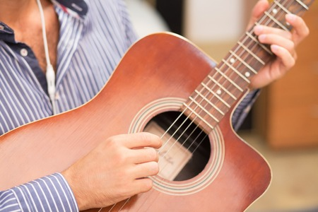 Front view of guitar in mans hands while he is playing at home. Handsome man playing his own music.