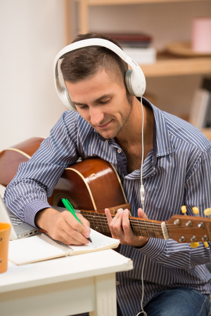 Picture of handsome man in white earphones playing guitar at home. Happy man writing new songs. Music concept.