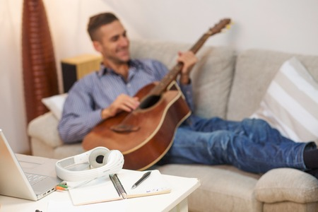Closeup portrait of white earphones represented on table while handsome man playing guitar at home. Music concept. Stock Photo