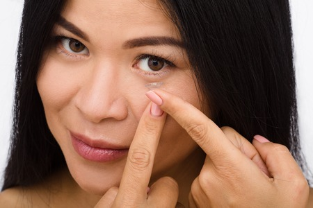 nearsighted: Closeup of woman putting contact lenses over white background. Lady putting lenses and looking at camera.