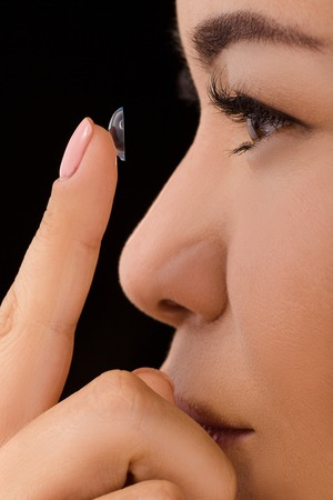 nearsighted: Closeup profile of beautiful woman holding point finger in front of her eyes. Lady imagining as if putting on contact lenses. Stock Photo