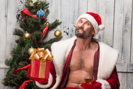 rudeness: Portrait of bad Santa Clause prefers drinking alcohol drinks and smoking sigars. Bad habits of bad Santa Clause in studio. Stock Photo