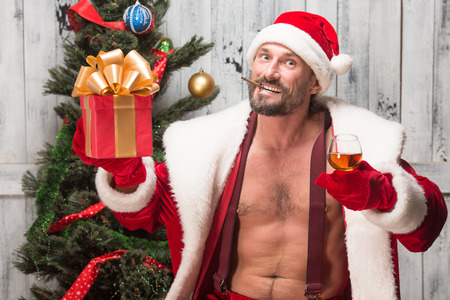 rudeness: Portrait of happy bad Santa Clause smoking sigars,drinking alcohol drinks and looking at camera isolated on white background.