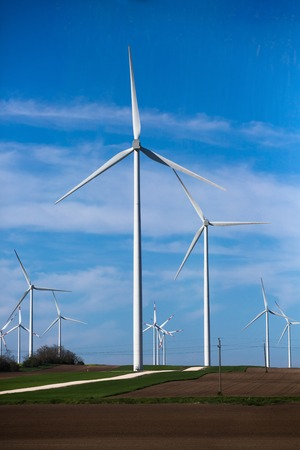 energy picture: Green meadow with wind turbines generating electricity. Picture of many wind turbines on field. Green energy concept.
